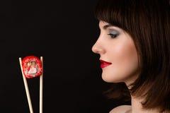 有筷子和卷的美丽的外形面孔妇女 免版税库存照片