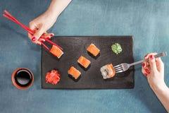 有筷子和叉子的两只妇女手 免版税库存照片