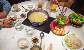 有筷子和白色饭桌的手 库存图片
