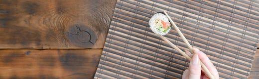 有筷子的一只手拿着在竹秸杆serwing的席子背景的寿司卷 亚洲食物炒饭传统蔬菜 免版税库存图片