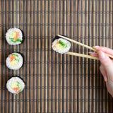 有筷子的一只手拿着在竹秸杆serwing的席子背景的寿司卷 亚洲食物炒饭传统蔬菜 库存照片