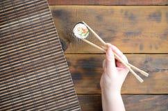 有筷子的一只手拿着在竹秸杆serwing的席子背景的寿司卷 亚洲食物炒饭传统蔬菜 库存图片