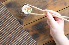 有筷子的一只手拿着在竹秸杆serwing的席子背景的寿司卷 亚洲食物炒饭传统蔬菜 免版税图库摄影