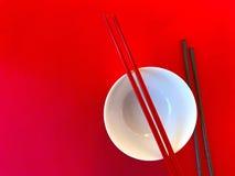 有筷子的白色碗在红色 免版税库存照片