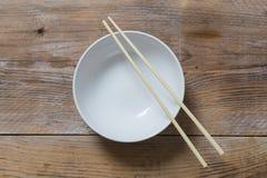 有筷子的碗在木概略的看法 免版税库存照片