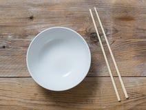 有筷子的碗在木概略的看法 免版税库存图片