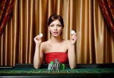 有筹码的妇女在轮盘赌表 图库摄影