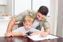 有算术家庭作业的微笑的父亲帮助的儿子在桌上 库存图片