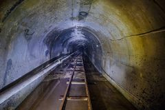 有管子和狭窄测量仪铁路的被放弃的被充斥的地下技术矿隧道 库存图片