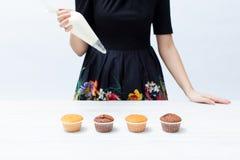 有管道系统的袋子的与奶油,在白色木桌上的杯形蛋糕女孩厨师 库存图片