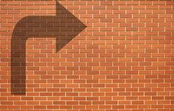 有箭头的现代红砖墙壁在砖墙上 库存照片