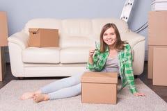 有箱子和把握的平的关键少妇 免版税库存图片