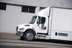 有箱子拖车的白色中间力量大小半卡车delive的城市的 图库摄影