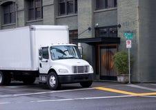 有箱子拖车的白色mddle半大小交付卡车在城市st 免版税库存照片