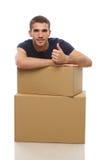 有箱子的一个年轻人在上面显示手指 库存图片