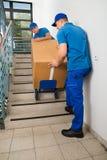 有箱子的两名搬家工人在楼梯 免版税图库摄影