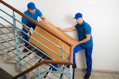 有箱子的两名搬家工人在楼梯 免版税库存照片