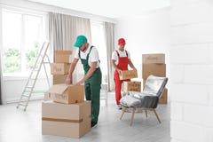有箱子的公搬家工人在房子里 免版税库存照片