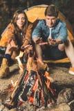 有篝火的夫妇温暖的手 库存照片