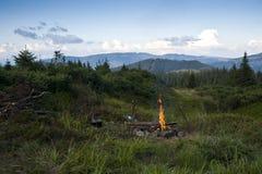有篝火的草甸在喀尔巴阡山脉 免版税库存图片