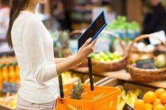 有篮子和片剂个人计算机的妇女在市场上 免版税库存照片