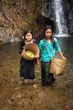有篮子的亚裔女孩在热带瀑布附近的雨林 库存照片