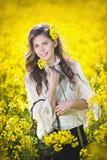 有篮子的俏丽的女孩微笑在油菜籽领域的 免版税库存图片