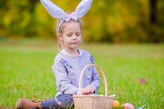 有篮子的可爱的小女孩佩带的兔宝宝耳朵有很多复活节彩蛋在春日户外 免版税库存图片