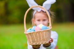 有篮子的可爱的小女孩佩带的兔宝宝耳朵有很多复活节彩蛋在春日户外 免版税库存照片