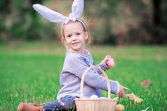 有篮子的可爱的小女孩佩带的兔宝宝耳朵有很多复活节彩蛋在春日户外 库存照片