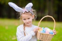 有篮子的可爱的小女孩佩带的兔宝宝耳朵有很多复活节彩蛋在春日户外 免版税图库摄影