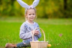 有篮子的可爱的小女孩佩带的兔宝宝耳朵有很多复活节彩蛋在春日户外 库存图片