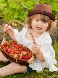有篮子的可爱的小女孩有很多stawberry 免版税库存图片