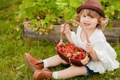 有篮子的可爱的小女孩有很多stawberry 库存图片