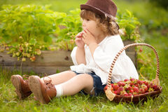 有篮子的可爱的小女孩有很多stawberry 库存照片