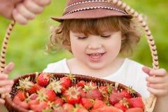 有篮子的可爱的小女孩有很多stawberry 免版税库存照片