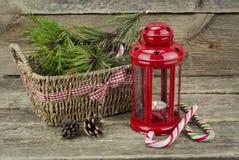 有篮子的圣诞节灯笼和在一木backg的一个棒棒糖 免版税库存照片