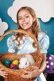有篮子的小女孩用颜色鸡蛋和白色复活节兔子 免版税库存图片