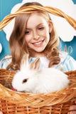 有篮子的小女孩用颜色鸡蛋和白色复活节兔子 免版税库存照片