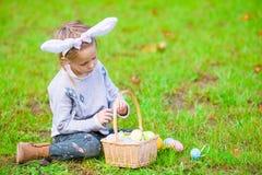 有篮子的小孩佩带的兔宝宝耳朵画象有很多复活节彩蛋在春日户外 免版税库存照片