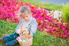 有篮子的小孩佩带的兔宝宝耳朵画象有很多复活节彩蛋在春日户外 库存照片