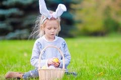 有篮子的小孩佩带的兔宝宝耳朵画象有很多复活节彩蛋在春日户外 免版税库存图片
