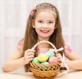 有篮子的微笑的小女孩有很多五颜六色的复活节彩蛋 库存照片