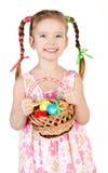 有篮子的微笑的小女孩有很多五颜六色的复活节彩蛋iso 库存照片