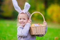 有篮子的愉快的小女孩佩带的兔宝宝耳朵有很多复活节彩蛋在春日户外 库存照片