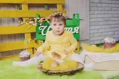 有篮子的愉快的小女孩小鸡坐室内 文本幸福 库存照片