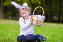 有篮子的有吸引力的小女孩佩带的兔宝宝耳朵有很多复活节彩蛋在春日户外 图库摄影