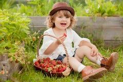 有篮子的白肤金发的卷毛头发小孩女孩有很多stawberry, 库存照片