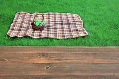 有篮子的空的野餐桌特写镜头毯子在Backgroun 免版税库存图片