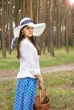 有篮子的美丽的女孩在森林里 免版税库存图片